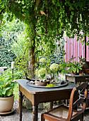 Kleiner Sitzplatz mit Hortensienblüten als Tischdekoration