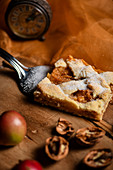 A piece of apple pie with cinnamon and nuts on a cake slice
