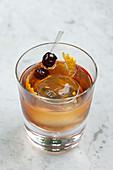 Whiskycocktail mit Eisball und Orangenschale