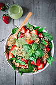Quinoa salad with strawberries, spinach and avocado dressing (top view)
