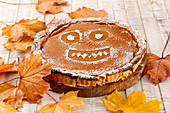 Pumpkin pie decorated with an icing sugar face