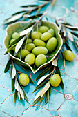 Green olives in a small bowl with olive branches