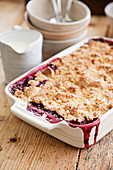 Apple and blackberry crumble with a jug of cream and bowls to serve