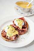 Poached eggs with hollandaise sauce on top of bacon and a muffin