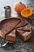 Sliced pumpkin tart with pumpkins in background