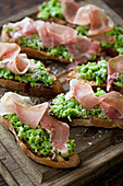Mashed broad beans on toast topped with parma ham and parmesan