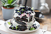 Charcoal pancakes with blueberries and vegan cream