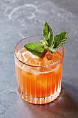 Oranger Cocktail mit Minzblättern