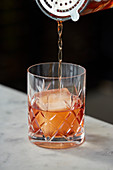 An Old Fashioned being poured