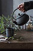 Tee aus einer Metallkanne einschenken