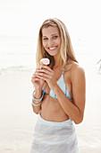 Blonde Frau mit Eis im Bikini am Strand