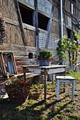 Alter Holztisch und Hocker als Sitzplatz im Garten, Chrysantheme in Schüssel auf dem Tisch