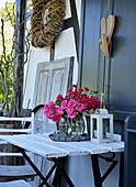 Rosenstrauß in Glasvase auf Gartentisch, Herzen aus Holz