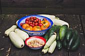 Frisch geerntete weiße Zucchini, Gurken, Physalis, Fleischtomaten und Cocktailtomaten