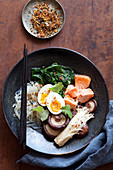 Gluten-free Buddha Bowl with mushrooms, vegetables, salmon and egg (Asia)