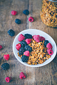 Granola with raspberries and blackberries, on a wooden surface