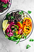 Vegan burrito bowls with spicy black beans, rice, summer vegetables, and pickled onons