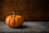 Mini orange pumpkin on a warn stone surface with rustic, brown, leather background