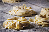 Variety of italian homemade raw uncooked pasta spaghetti and tagliatelle with sprinkling semolina flour