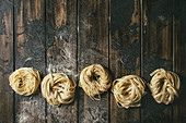Variety of italian homemade raw uncooked pasta spaghetti and tagliatelle in row with semolina flour on wooden table