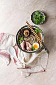 Traditional Japanese Noodle Soup with shiitake mushroom, egg, sliced beef and greens in ceramic bowl with wooden chopsticks