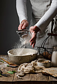 A woman sifting flour into a bowl to make pumpkin scones