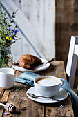 A cup of coffee with a croissant on a rustic wooden table in a country kitchen