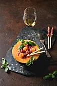 Melone serviert mit Schinken, Grissinis und Basilikum dazu ein Glas Weißwein