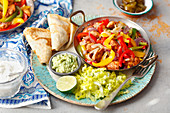 Chicken with pepper and onion, pancakes, guacamole