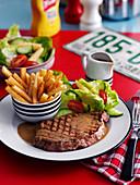 Rindersteak mit Pommes und Salat im Diner