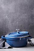 A steaming blue pot against a grey background
