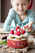 A boy sitting in front of mini cheesecakes in a biscuit tin decorated with strawberry Christmas hats
