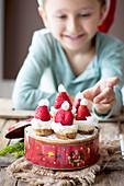 Junge sitzt vor Mini-Käsekuchen in Keksdose dekoriert mit Weihnachtsmützen aus Erdbeeren