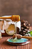 Honig fließt von Honiglöffel auf Teller