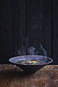Steaming hot broth in a dark earthenware bowl