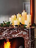 Weihnachtskerzen und Ilexzweige auf Kaminsims über offenem Kaminfeuer