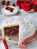 Classic Fondant Iced Christmas cake cut into with slice