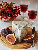 Gorganzola with fresh figs on a wooden cheese board