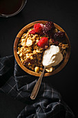 Granola with raspberries and blackberries and a spoon of cream in wooden bowl with a cup of coffee on black table