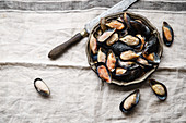 Frozen mussels in metallic vintage plate on linen tablecloth with stripes