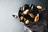 Fresh mussels in black ceramic bowl on dark concrete background