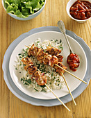 Chicken skewers on parsley rice with tomato salsa