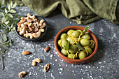 A bowl of green olives wth mixed nuts