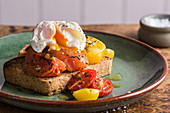 A slice of bread topped with roasted tomatoes and a poached egg