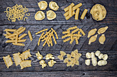 Various types of pasta on a wooden surface