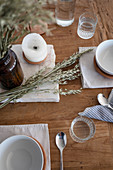 Gedeck, Kerze und Getreideähren auf rustikalem Holztisch