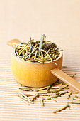 Japanese green tea leaves in a wooden measuring spoon