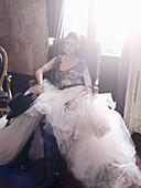 Junge brünette Frau in spanischen Abendkleid sitz auf Stul in wohnlichem Ambiente