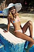 Junge brünette Frau in buntem Bikini und mit Sommerhut sitzt auf einem Badetuch an einem Pool