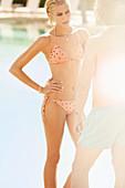 Junge blonde Frau mit kurzen Haaren im lachsfarbenen Bikini redet mit Mann
